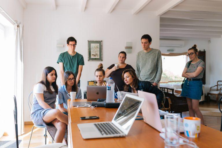 Flera elever bredvid ett bord fyllt av skolmaterial och laptops