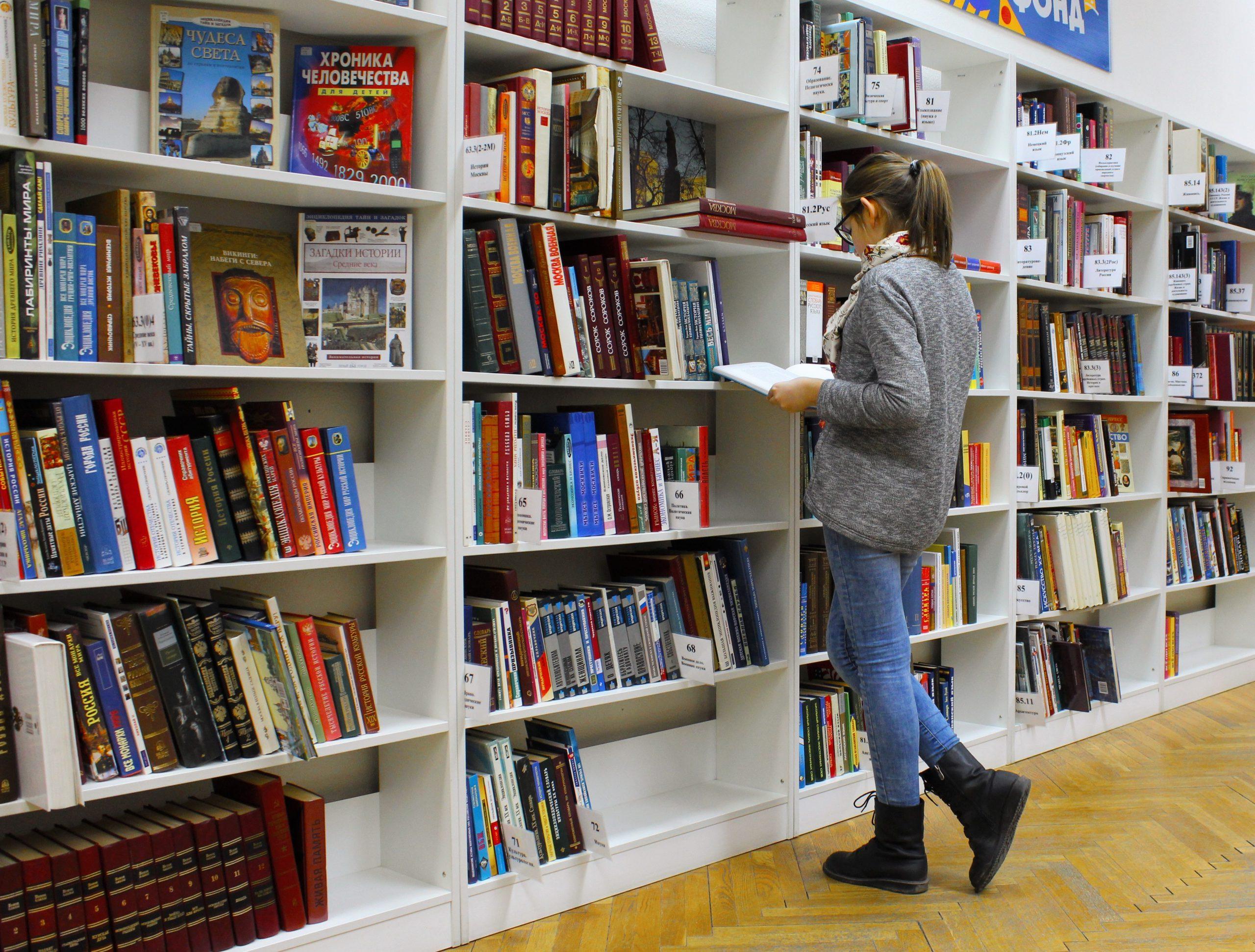Kvinna står framför flera bokhyllor fyllda med böcker