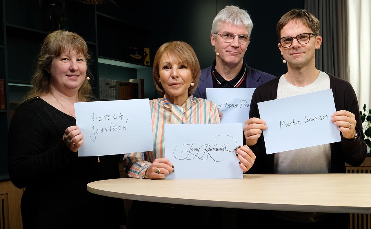 4 personer står med papper i händerna. På papperen står deras namn i handskrift.