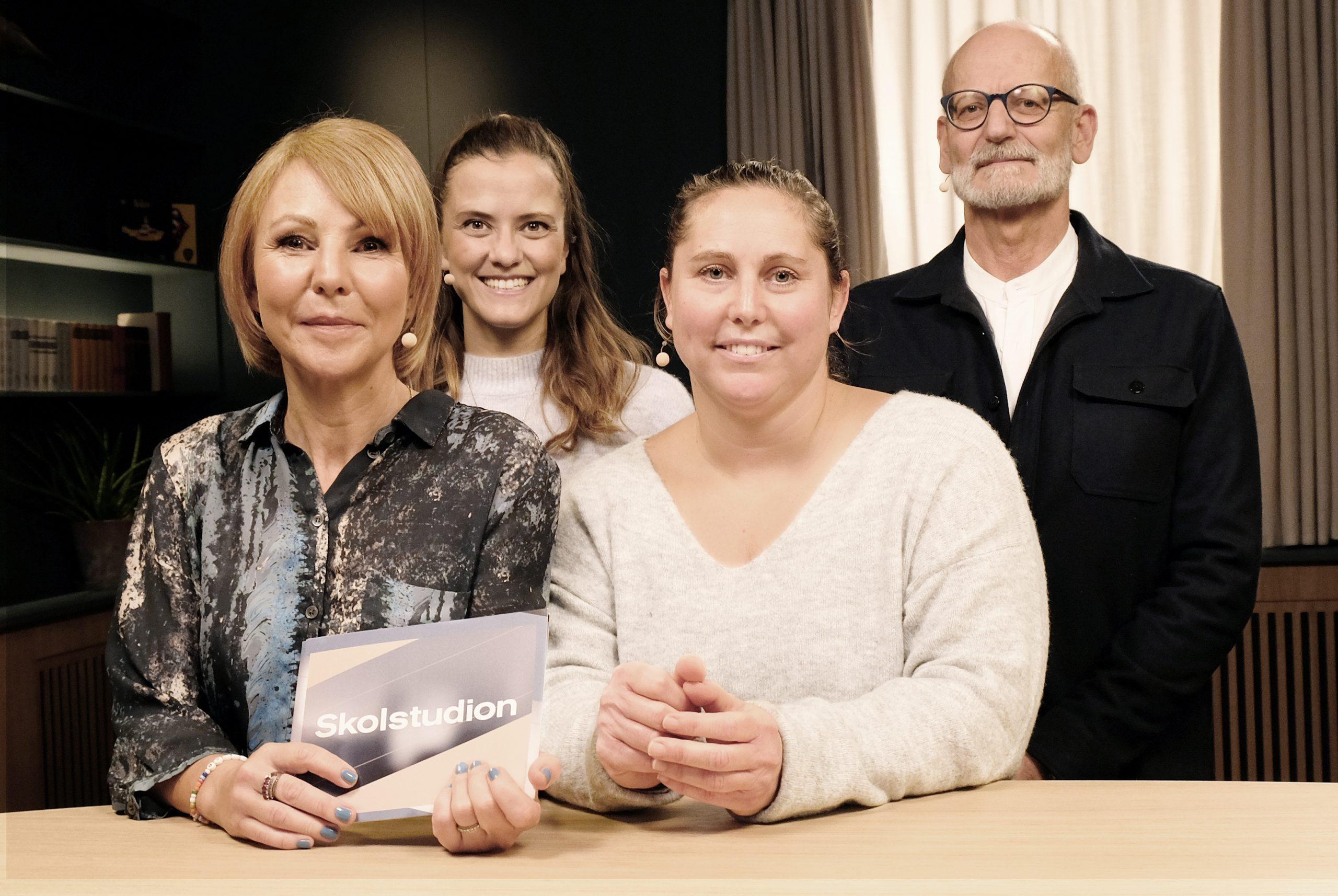 Fyra personer står bakom ett bord och tittar in i kameran.