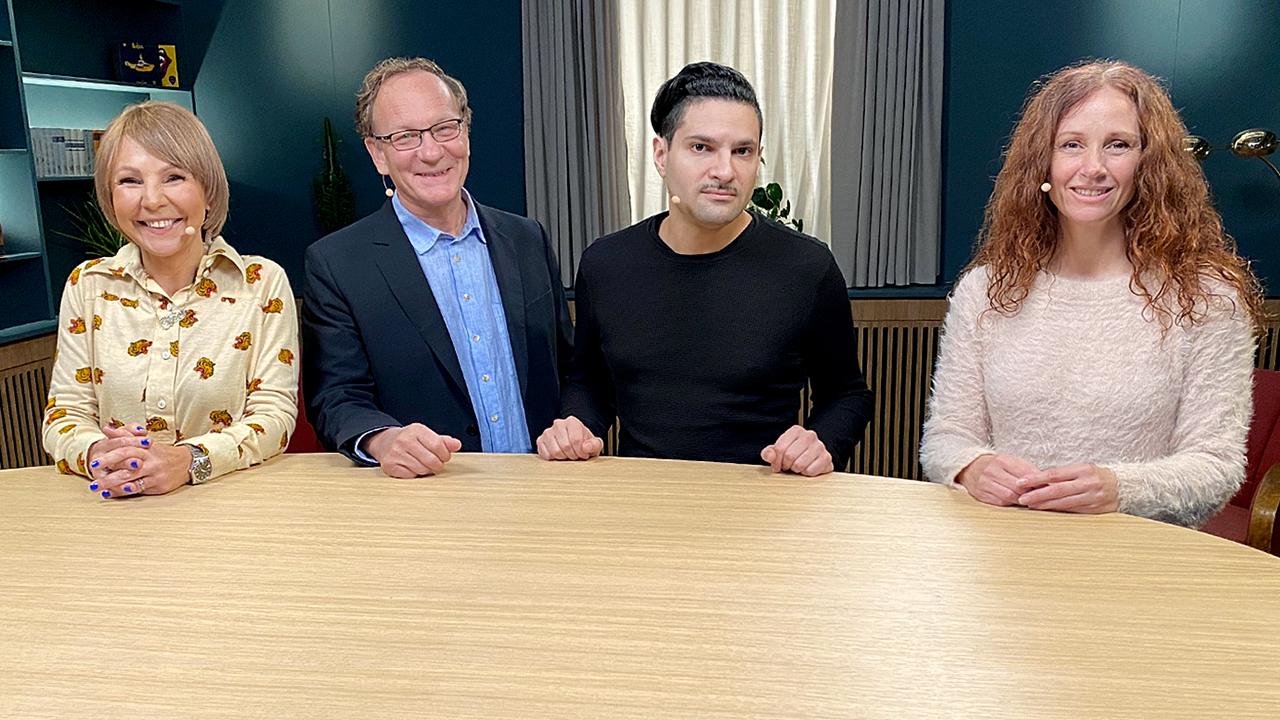 4 personer står bakom ett bord och ler mot kameran