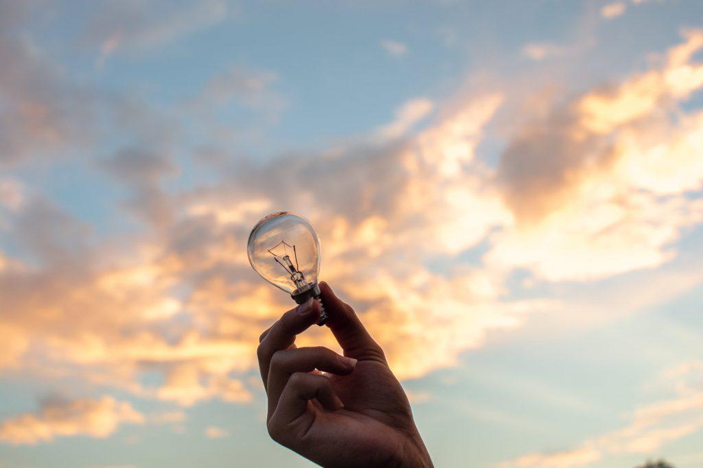 En hand håller i en glödlampa. I bakgrunden en vacker himmel med moln.