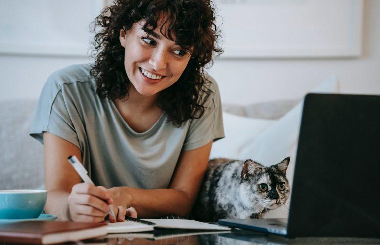 Kvinna sitter och antecknar framför sin laptop. En katt tittar också mot datorskärmen.