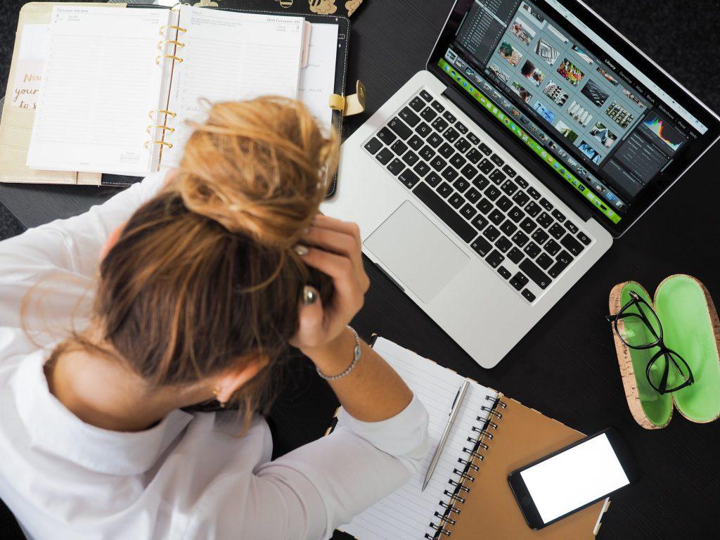Ung kvinna sitter vid laptop med huvudet vilande i händerna.