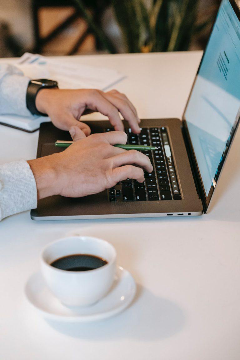 Två händer skriver på tangentbordet på en laptop. En kopp kaffe står i förgrunden.