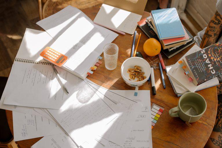 Ett bord fyllt av studiematerial och frukost.