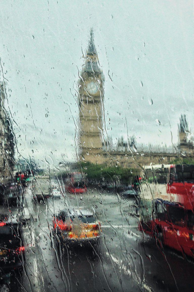 Fotografi av Big Ben och en bilväg tagen genom ett regnigt fönster.