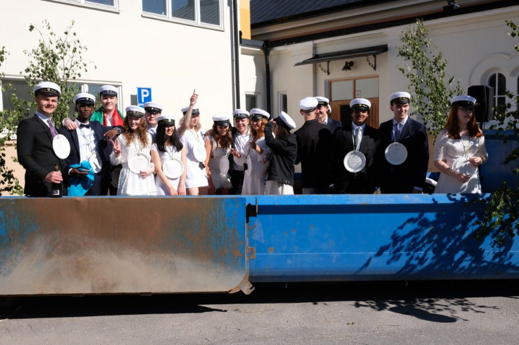 Studenter står i en blå container