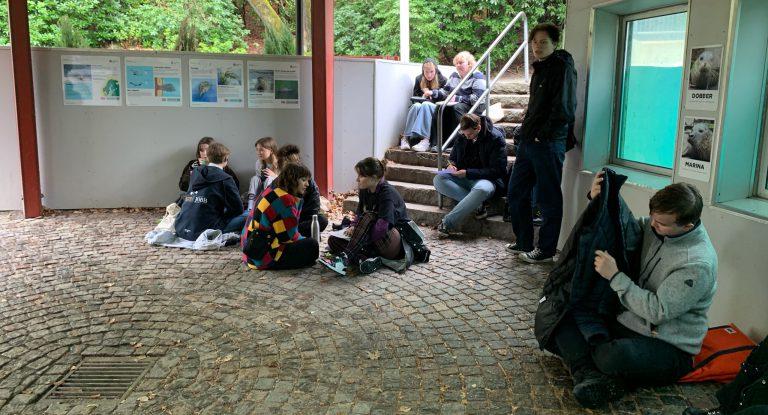 Elever sitter under en paviljong