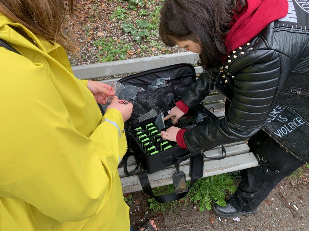 Två personer står böjda över en väska med teknik