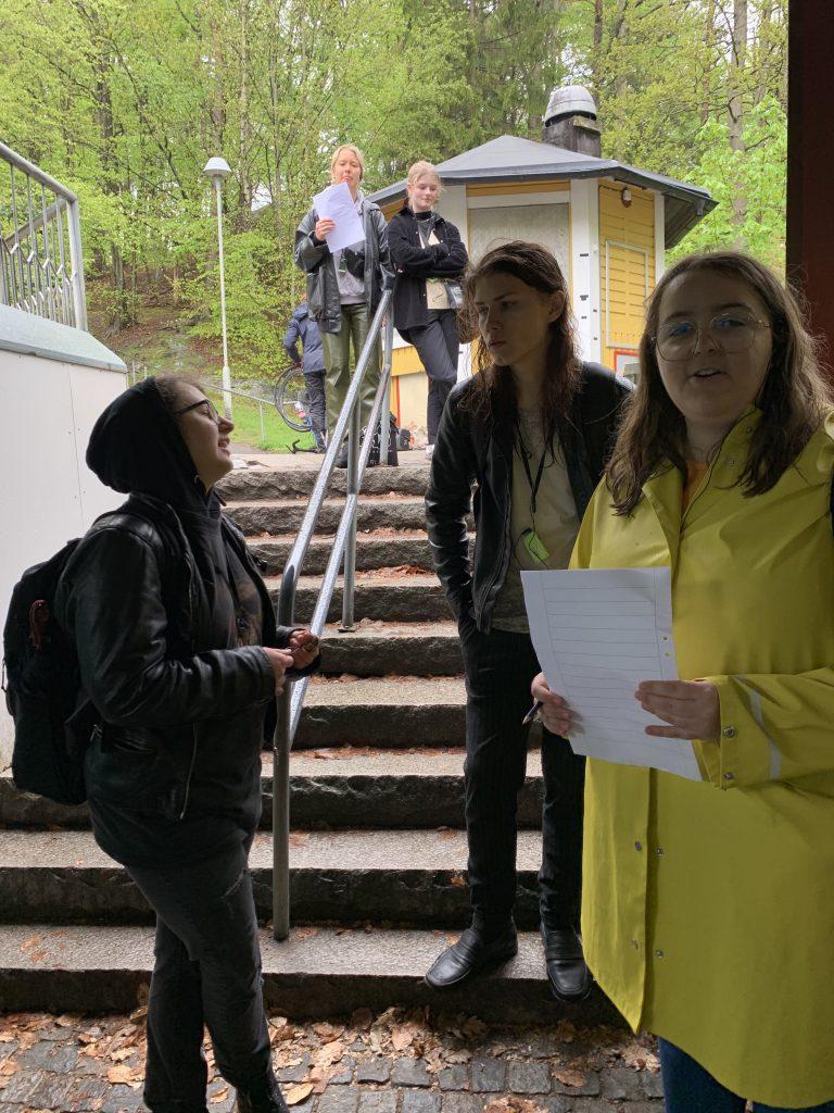 Elever står och samtalar i en trapp utomhus