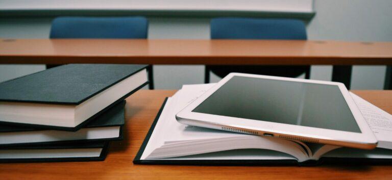 Böcker ligger uppslagna på en skolbänk med en iPad
